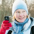 The woman photographes on a mobile phone in winter on walk — Stock Photo