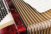 Red accordion and sheet music, close up — Stockfoto