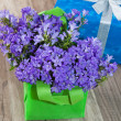 Spring bouquet campanula blue and gift box, a close up — Stock Photo