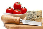 Chopping board with blue cheese and cherry tomatoes — Stock Photo