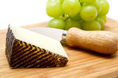 Manchego cheese ang grapes on chopping board — Stock Photo
