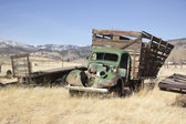 Old farm truck in a field of junk — Stock Photo