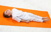 Baby yoga. The little boy does exercise. — Stock Photo