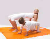 A beautiful young mother practices yoga with her son — Stock Photo