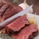 Roast beef with knife — Stockfoto