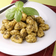 Gnocchi and pesto sauce - Stock Photo