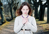 Young woman in vintage dress praying — Stock Photo