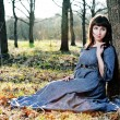 Young woman in medieval dress sitting near the tree — Stock Photo