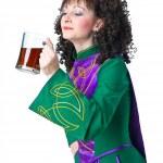Woman irish dancer drinking beer — Stock Photo