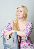 Blond woman sitting on the chair — Stock Photo