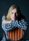 Man with long hair sitting on chair — Stock Photo