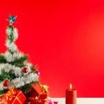 vánoční dárky se svíčkami na červeném pozadí — Stock fotografie