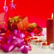 Christmas gifts with candles over red background — 图库照片