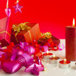 Foto Stock: Christmas gifts with candles over red background