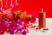 Christmas gifts with candles over red background — Stok fotoğraf