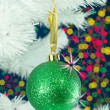 Green ball hanging on the Christmas tree - Stock Photo