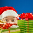 Surprised teen girl looking from behind the Christmas presents — Stock Photo #8072576