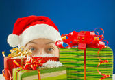 Surprised teen girl looking from behind the Christmas presents — Stock Photo