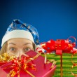 Surprised teen girl looking from behind the Christmas presents — Stock Photo #8173917