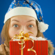 Surprised teen girl looking from behind the Christmas present — Stock Photo #8174352