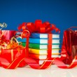 Christmas presents with stack of books against blue background — Stock Photo