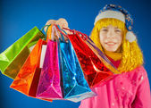 Teen girl holds a variety of colorful bags against blue background — Stock Photo