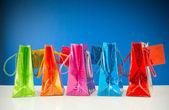 青い背景とカラフルな袋の行 — ストック写真