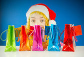 Teen girl looking from behind a row of colorful bags — Stock Photo
