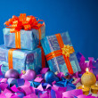 Christmas gifts and candles over blue background — Stock Photo