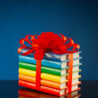 Stack of colorful books tied up with red ribbon — Stock Photo