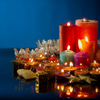 A lot of burning colorful candles against dark blue background — Stock Photo