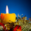 Burning candle with Christmas decorations against blue background — Stock Photo