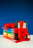 Books tied up with ribbon and electronic book reader against blue backgroun — Stock Photo