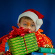 Surprised boy looking from behind the Christmas presents — Stock Photo