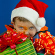 Surprised boy looking from behind the Christmas presents — Stock Photo #8320881