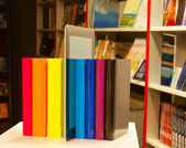 Row of colorful books and tablet PC reader in the book shop — Stock Photo