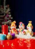 Three snowmen and burning candles over the blue background — Стоковое фото