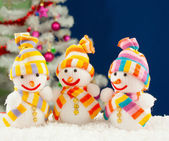 Three snowmen in front of the decorated white evergreen tree ove — Stock Photo
