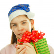 Teen girl wearing Santa hat with a present against white backgro — Stock Photo #8409296