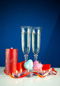 Two wineglasses and burning candles against blue background — Stock Photo