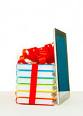 Books tied up with ribbon and tablet PC against white background — Stock Photo