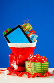 Tablet PC with heap of presents in red bag against blue backgrou — Stok fotoğraf