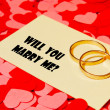 Stock Photo: Two rings and card with marriage proposal