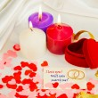 Stock Photo: Two rings and card with marriage proposal with three candles