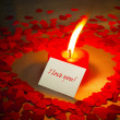 Burning heart shaped candle and a card - Stok fotoraf
