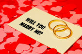 Two rings and a card with marriage proposal — Stock Photo