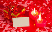 Present and two heart shaped candles with blank card — Stock Photo