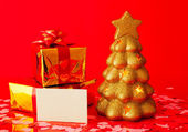 Two presents, blank card and golden evergreen tree — Stock Photo