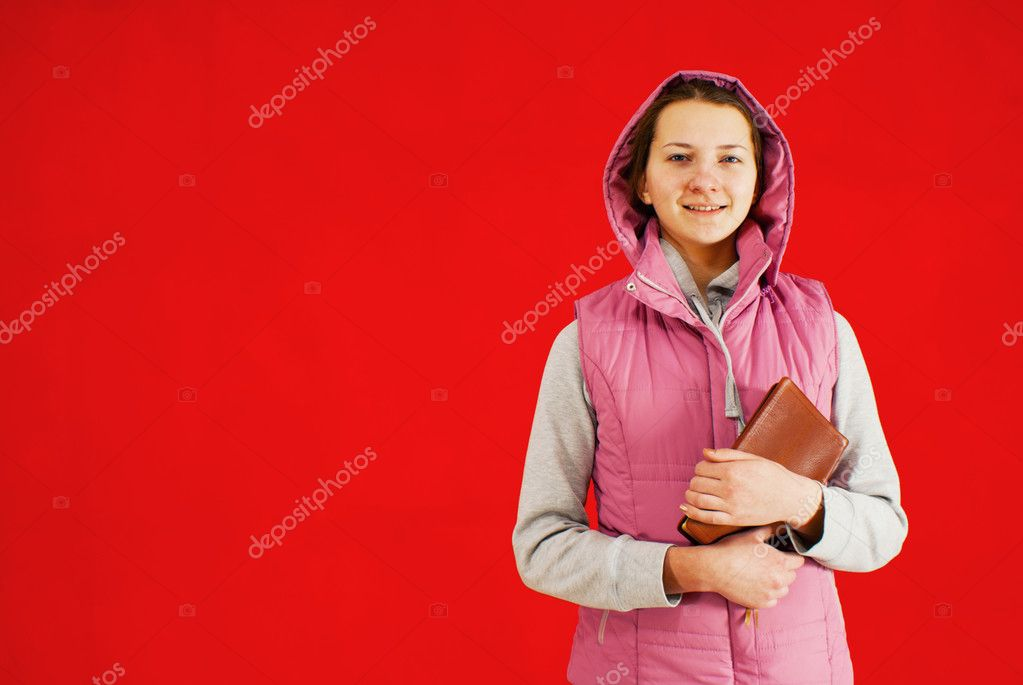 Teen girl staying with a book against red background  Stock Photo #8686698