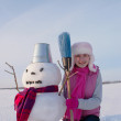 Teenage girl with snowman — Stock Photo